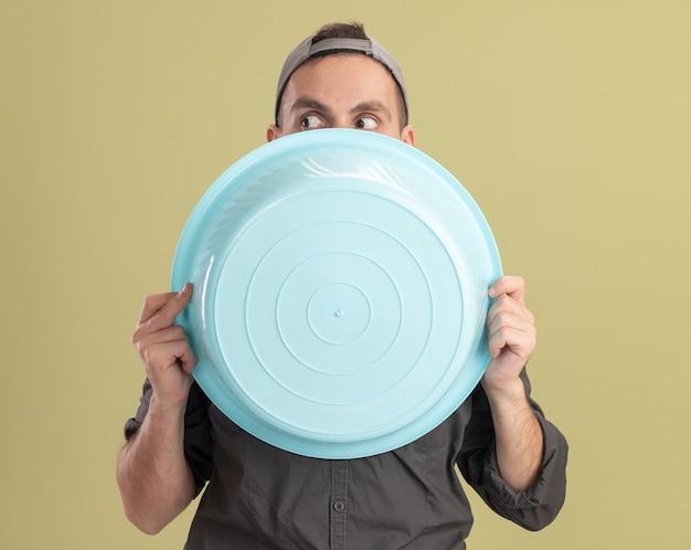 Giovane uomo delle pulizie che indossa abiti casual e berretto tenendo il bacino nascondendo il viso dietro di esso che dà una occhiata in piedi sopra la parete verde