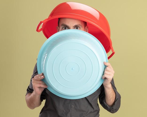 Giovane uomo delle pulizie che indossa abiti casual e berretto tenendo il bacino e sulla sua testa che dà una occhiata sopra in piedi sopra il muro verde