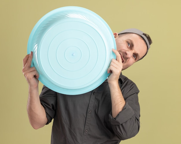 Giovane uomo delle pulizie che indossa abiti casual e berretto tenendo il bacino con espressione infastidita in piedi sopra la parete verde