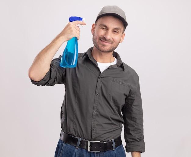 Giovane uomo delle pulizie che indossa abiti casual e berretto che tiene spray per la pulizia vicino al suo tempio sorridendo allegramente in piedi sopra il muro bianco