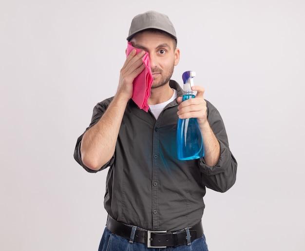 Giovane uomo delle pulizie che indossa abiti casual e berretto che tiene spray per la pulizia e straccio asciugandosi gli occhi con uno straccio in piedi sul muro bianco