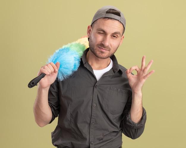 Giovane uomo delle pulizie che indossa abiti casual e berretto che tiene spolverino colorato che sembra felice e allegro che mostra segno giusto in piedi sopra la parete verde