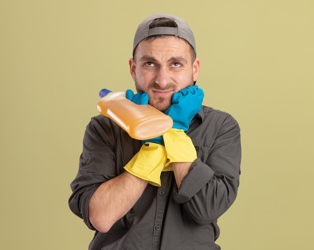 Giovane uomo delle pulizie che indossa abiti casual e berretto in guanti di gomma tenendo la bottiglia con prodotti per la pulizia che sembrano confusi e scontenti in piedi sopra la parete verde