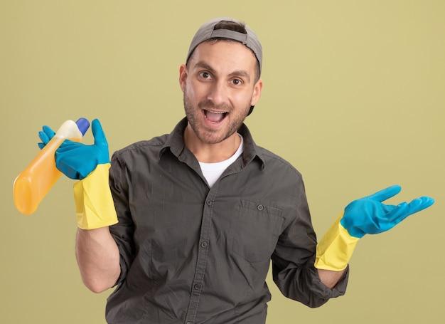Giovane uomo delle pulizie che indossa abiti casual e berretto in guanti di gomma tenendo la bottiglia con prodotti per la pulizia che sembrano sorridenti felici e positivi in piedi sopra la parete verde