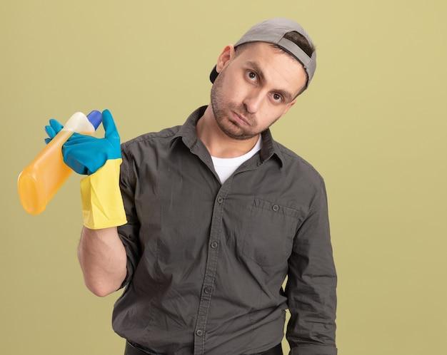 Giovane uomo delle pulizie che indossa abiti casual e berretto in guanti di gomma tenendo la bottiglia con prodotti per la pulizia che sembrano stanchi e infastiditi in piedi sopra la parete verde