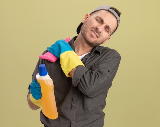 Young cleaning man wearing casual clothes and cap in rubber gloves holding bottle with cleaning supplies and rag touching his shoulder feeling pain standing over green wall