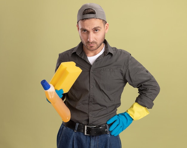 Giovane uomo delle pulizie che indossa abiti casual e berretto in guanti di gomma tenendo la bottiglia con prodotti per la pulizia e spugna guardando con faccia seria in piedi sopra la parete verde