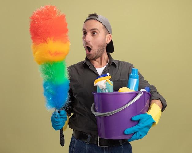 Giovane uomo delle pulizie che indossa abiti casual e berretto in guanti di gomma che tiene secchio con strumenti di pulizia e spolverino colorato guardandolo stupito e sorpreso in piedi sopra la parete verde