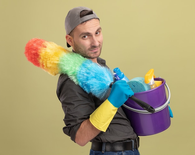 Giovane uomo delle pulizie che indossa abiti casual e berretto in guanti di gomma che tengono secchio con strumenti di pulizia e spolverino colorato guardando sorridente fiducioso in piedi sopra la parete verde