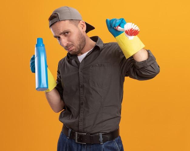 Giovane uomo delle pulizie che indossa abiti casual e berretto in guanti di gomma tenendo la spazzola per la pulizia e la bottiglia con prodotti per la pulizia che sembrano confusi e scontenti in piedi sopra la parete arancione