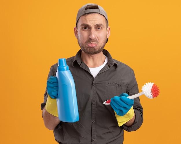 Giovane uomo delle pulizie che indossa abiti casual e berretto in guanti di gomma che tengono spazzola per la pulizia e bottiglia con prodotti per la pulizia guardando con espressione triste in piedi sopra la parete arancione