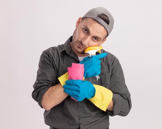 Giovane uomo delle pulizie che indossa abiti casual e berretto in guanti di gomma che tengono spray per la pulizia e straccio cercando stanco e annoiato in piedi sopra la parete arancione