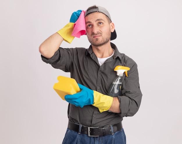 Giovane uomo delle pulizie che indossa abiti casual e berretto in guanti di gomma che tiene spray per la pulizia e spugna con uno straccio sulla sua spalla guardando perplesso in piedi sopra la parete arancione