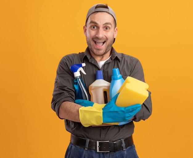 Giovane uomo delle pulizie che indossa abiti casual e berretto in guanti di gomma che tengono i prodotti per la pulizia e la spugna che sembrano felici ed eccitati in piedi sopra la parete arancione