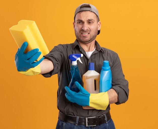 Giovane uomo delle pulizie che indossa abiti casual e berretto in guanti di gomma che tengono i prodotti per la pulizia e la spugna guardandolo con espressione delusa rendendo la bocca ironica in piedi sopra la parete arancione