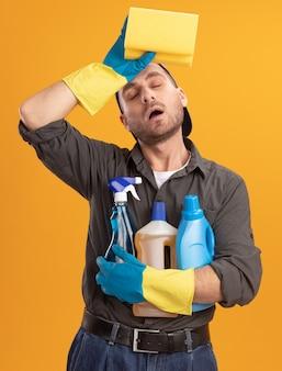 Giovane uomo delle pulizie che indossa abiti casual e berretto in guanti di gomma che tengono i prodotti per la pulizia e la spugna che sembra stanco e oberato di lavoro con la mano sulla fronte in piedi sopra la parete arancione