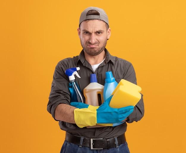 Giovane uomo delle pulizie che indossa abiti casual e berretto in guanti di gomma che tengono i prodotti per la pulizia e la spugna guardando con espressione delusa rendendo la bocca ironica in piedi sopra la parete arancione