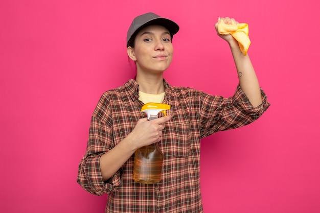 Giovane donna delle pulizie in abiti casual e berretto che tiene in mano uno straccio e uno spray per la pulizia sorridente fiduciosa pronta per la pulizia in piedi sul rosa