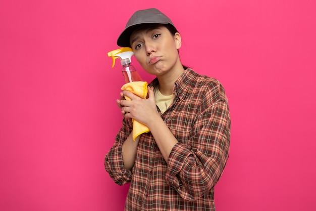 Giovane donna delle pulizie in abiti casual e berretto che tiene straccio e spray per la pulizia stanca con un'espressione triste sul viso in piedi sul muro rosa
