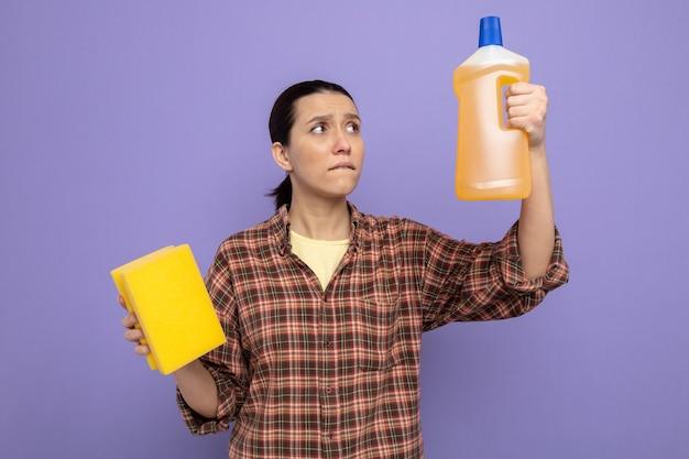 Giovane donna delle pulizie in abiti casual che tiene in mano una bottiglia di prodotti per la pulizia con una spugna che sembra confusa cercando di fare una scelta in piedi sul viola