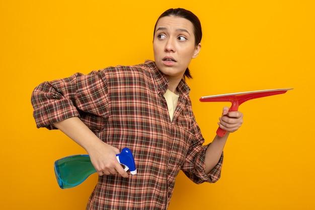 Giovane donna delle pulizie in abiti casual con in mano spray detergente e mocio che guarda da parte confusa e preoccupata in piedi sul muro arancione
