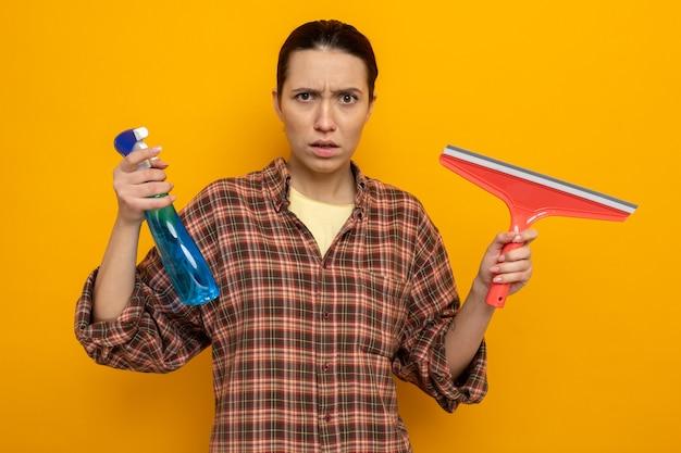 Giovane donna delle pulizie in abiti casual che tiene in mano uno spray detergente e una scopa che guarda con faccia seria