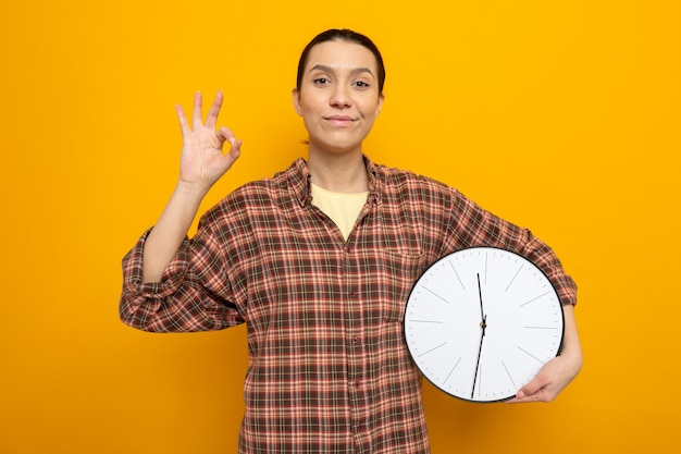 Young cleaning woman in casual clothes holding clock looking happy and positive showing ok sign