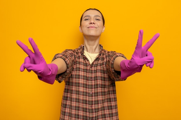 Giovane donna delle pulizie in abiti casual con guanti di gomma felice e positiva che mostra il v-sign