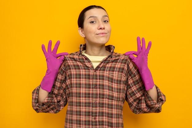 Giovane donna delle pulizie in abiti casual con guanti di gomma con espressione sicura che tocca la sua maglietta in piedi sul muro arancione