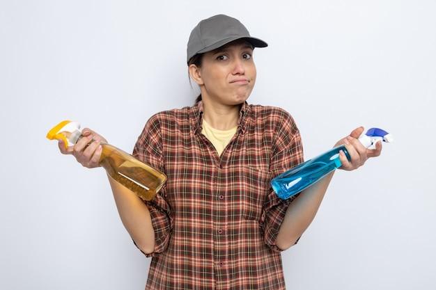 Молодая уборщица в повседневной одежде и кепке, держащая чистящие спреи, смущена, пожимая плечами, вызывая сомнения, стоя на белом