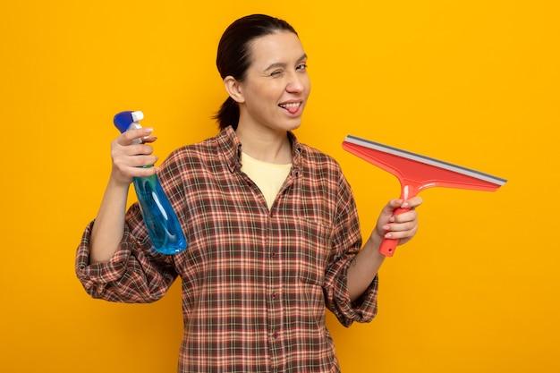청소 스프레이와 걸레를 들고 있는 평상복을 입은 젊은 청소 여성이 주황색 벽 위에 서 있는 행복하고 긍정적인 혀를 내밀고 있습니다.