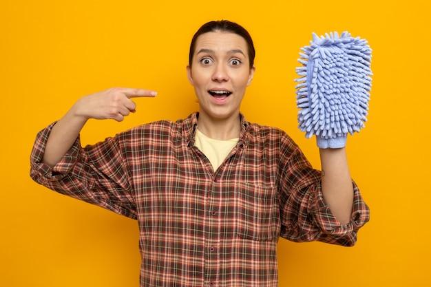 それを人差し指で指しているダスターを保持しているカジュアルな服を着た若い掃除婦は、オレンジ色の壁の上に立って驚いて笑っています