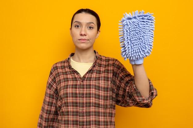 オレンジ色の壁の上に立っている自信を持って表情とダスターを保持しているカジュアルな服を着た若い掃除婦