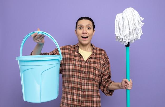 紫色の壁の上に元気に立って幸せで前向きな笑顔の正面を見てモップとバケツを保持しているカジュアルな服を着た若い掃除婦