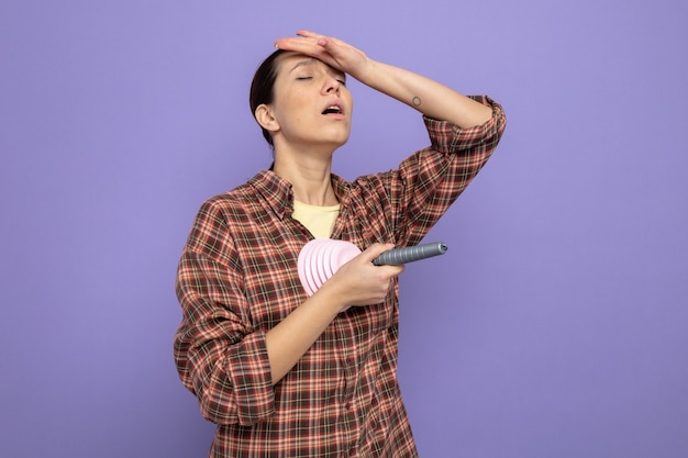 Молодая уборщица в повседневной одежде, держащая поршень, выглядит усталой и напряженной, положив руку на лоб, стоя на фиолетовом