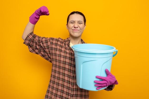 オレンジ色の上に立っている幸せで興奮した握りこぶしを保持しているゴム手袋でカジュアルな服を着た若い掃除婦