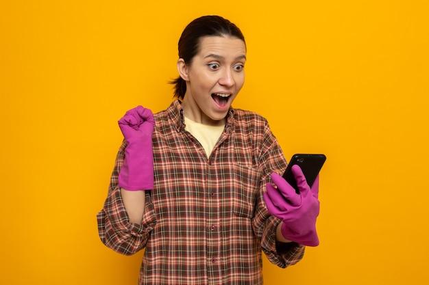 고무장갑을 끼고 평상복을 입은 젊은 청소 여성이 주황색 벽 위에 서서 행복하고 흥분된 주먹을 들고 휴대폰을 바라보고 있다