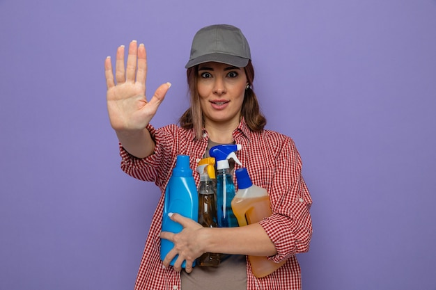 Молодая уборщица в клетчатой рубашке и кепке, держащая бутылки с моющими средствами, смотрит в камеру с серьезным лицом, делая стоп-жест рукой, стоящей на фиолетовом фоне