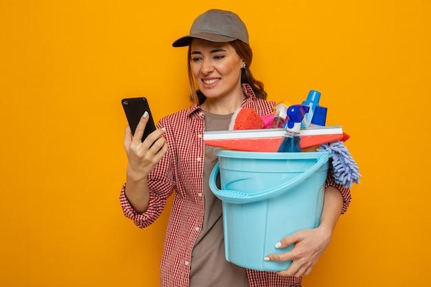 オレンジ色の背景の上に立ってイライラしている彼女の携帯電話を見ているクリーニングツールでバケツを保持している格子縞のシャツと帽子の若いクリーニング女性