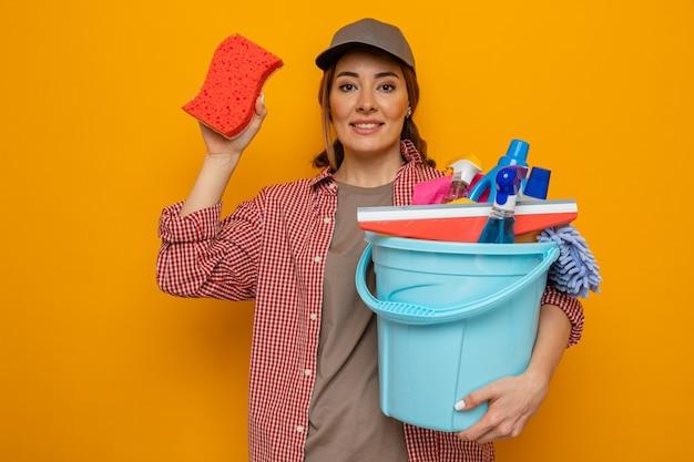 Молодая уборщица в клетчатой рубашке и кепке, держащая ведро с чистящими средствами, показывает губку, уверенно улыбаясь, глядя в камеру, стоящую на оранжевом фоне
