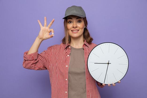 Молодая уборщица в клетчатой рубашке и кепке держит часы, глядя, что делает хорошо, знак весело улыбается