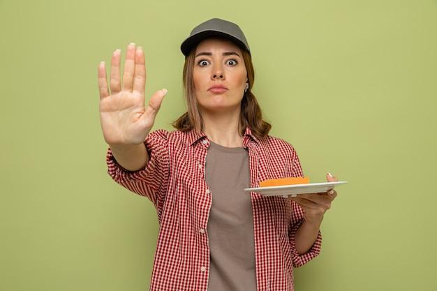 Молодая уборщица в клетчатой рубашке и кепке, держащая тарелку и губку, смотрит в камеру с серьезным лицом, делая стоп-жест рукой, стоящей на зеленом фоне