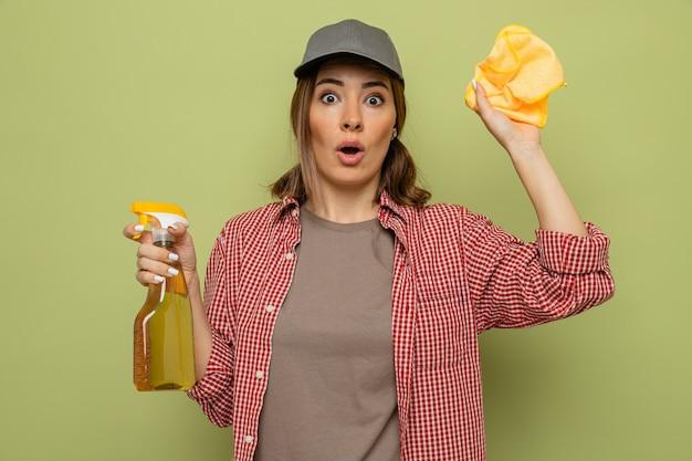 緑の背景の上に立って驚いたカメラを見てぼろきれとクリーニングスプレーを保持している格子縞のシャツと帽子の若いクリーニング女性