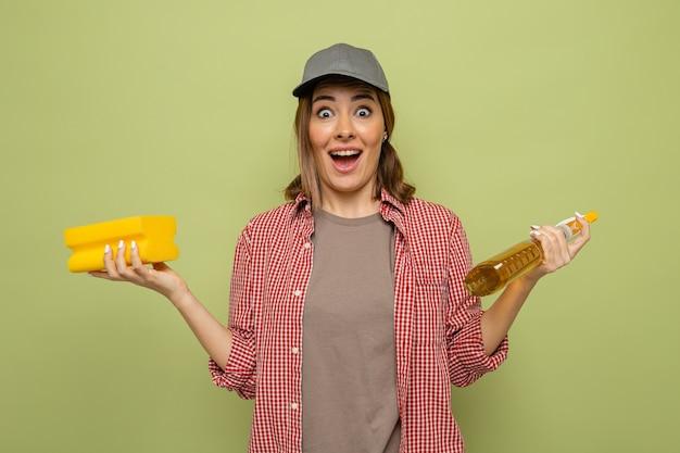 緑の背景の上に立って幸せで驚いたカメラを見てスポンジとクリーニングスプレーを保持している格子縞のシャツと帽子の若いクリーニング女性