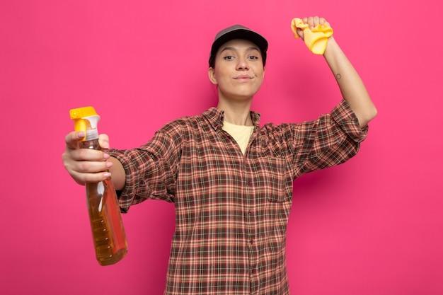 格子縞のシャツとゴム手袋の帽子をかぶった若い掃除婦がスポンジと掃除スプレーを持って笑顔で自信を持って掃除の準備ができているように見えます