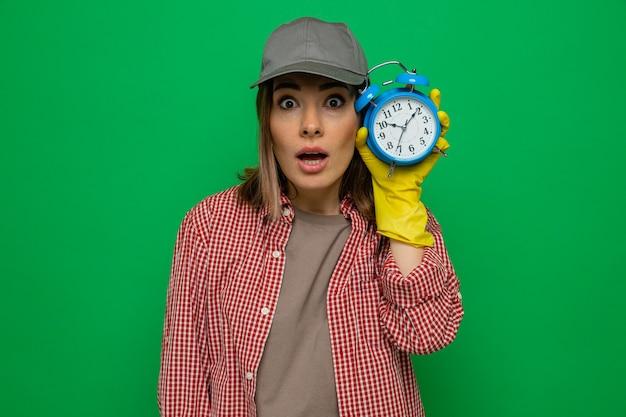 체크 무늬 셔츠와 모자를 쓴 젊은 청소 여성은 알람 시계를 들고 녹색 배경 위에 서서 걱정스럽게 카메라를 쳐다보고 있다