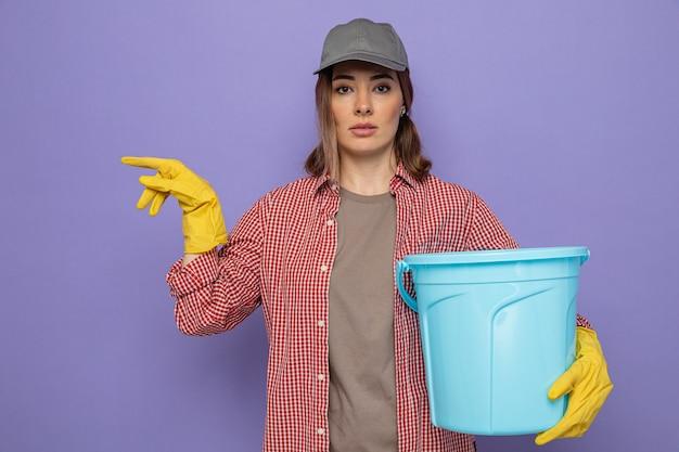 보라색 배경 위에 서있는 측면에 검지 손가락으로 가리키는 심각한 얼굴로 카메라를보고 양동이를 들고 고무 장갑을 끼고 격자 무늬 셔츠와 모자에 젊은 청소 여자