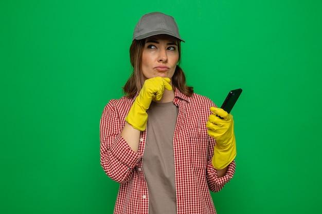 緑の背景の上に立って困惑して見上げるスマートフォンを保持しているゴム手袋を身に着けている格子縞のシャツと帽子の若い掃除婦