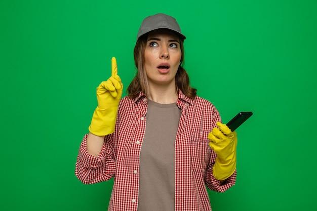 격자 무늬 셔츠와 고무 장갑을 끼고 모자를 쓴 젊은 청소 여성이 스마트폰을 들고 녹색 배경 위에 새로운 아이디어가 있는 집게 손가락을 보여줍니다
