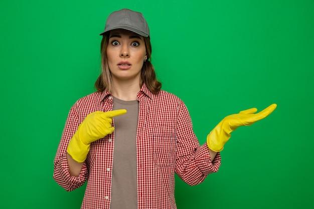 緑の背景の上に立っている彼女の腕に人差し指で指している彼女の手の腕を提示して混乱しているカメラを見て、格子縞のシャツとゴム手袋を身に着けている若い掃除婦